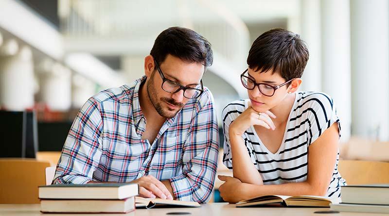 Um professor com óculos, camisa xadrez, lendo um livro para a aluna, que também esta de óculos, e uma blusa listrada, apoiada em um livro aberto