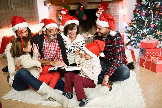 Uma família, quatro adultos, com gorro de papai Noel, duas crianças, sentados em um tapete no chão, ao lado de uma arvore de natal, e presentes