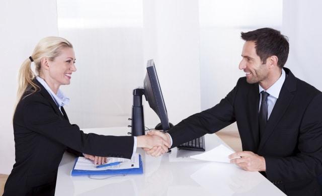 Um homem de terno, camisa social e gravata, cumprimentando uma mulher loira, com o cabelo amarrado, vestindo camisa social e blazer