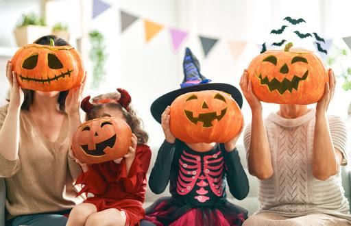 Duas mulheres, e duas crianças, segurando abobora de dia das bruxas, em frente ao rosto