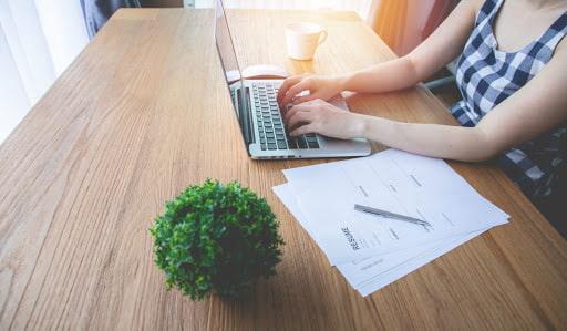 Uma mulher, de blusa xadrez, com os braços apoiados sobre a mesa, digitando no notebook, ao lado algumas folhas de papel, em baixo de uma caneta.